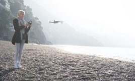 Young girl flying drone over italian coast. stock photography