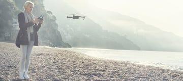 Young girl flying drone over italian coast. stock photos
