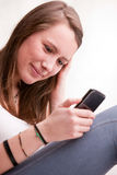 Young girl focused on texting with mobile Stock Photo
