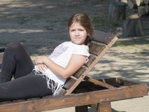 Young girl on a folding chair royalty free stock photo
