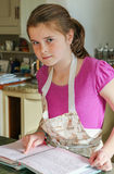 Young girl following a recipe book while baking. A 9 year old girl following a recipe book in an apron whilst baking Royalty Free Stock Photo