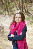 Young girl in a forest. Cute young girl in a forest wearing a pink scarf Stock Image