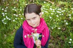 Young girl in a forest. Cute young girl in a forest wearing a pink scarf and a white flower behind her ear Royalty Free Stock Photography