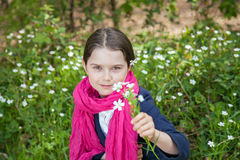 Young girl in a forest. Cute young girl in a forest wearing a pink scarf and a white flower behind her ear Stock Photography