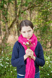 Young girl in a forest. Cute young girl in a forest wearing a pink scarf and a white flower behind her ear Royalty Free Stock Images