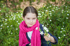 Young girl in a forest. Cute young girl in a forest wearing a pink scarf and a white flower behind her ear Royalty Free Stock Image