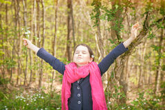 Young girl in a forest. Cute young girl in a forest wearing a pink scarf and a white flower behind her ear Stock Photo