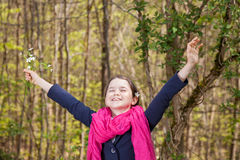 Young girl in a forest. Cute young girl in a forest wearing a pink scarf and a white flower behind her ear Royalty Free Stock Photo