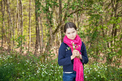Young girl in a forest. Cute young girl in a forest wearing a pink scarf and a white flower behind her ear Stock Images