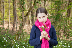 Young girl in a forest. Cute young girl in a forest wearing a pink scarf and a white flower behind her ear Royalty Free Stock Photos