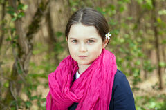 Young girl in a forest. Cute young girl in a forest wearing a pink scarf and a white flower behind her ear Stock Photos