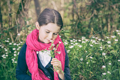 Young girl in a forest. Cute young girl in a forest wearing a pink scarf and a white flower behind her ear - vintage style Stock Images