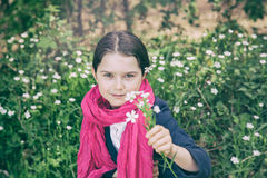 Young girl in a forest. Cute young girl in a forest wearing a pink scarf and a white flower behind her ear- vintage style Stock Photos