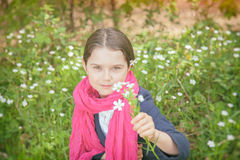 Young girl in a forest. Cute young girl in a forest wearing a pink scarf and a white flower behind her ear- vintage style Royalty Free Stock Photo