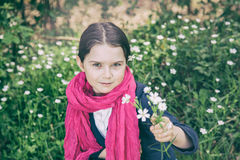 Young girl in a forest. Cute young girl in a forest wearing a pink scarf and a white flower behind her ear- vintage style Royalty Free Stock Photography