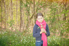 Young girl in a forest. Cute young girl in a forest wearing a pink scarf and a white flower behind her ear- vintage style Royalty Free Stock Images