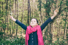 Young girl in a forest. Cute young girl in a forest wearing a pink scarf and a white flower behind her ear- vintage style Stock Image