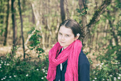 Young girl in a forest. Cute young girl in a forest wearing a pink scarf and a white flower behind her ear- vintage style Royalty Free Stock Photos
