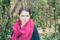 Young girl in a forest. Cute young girl in a forest wearing a pink scarf and a white flower behind her ear- vintage style Stock Photo