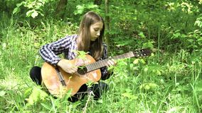 Girl playing the guitar. Young girl in forest with guitar in the garden. Teenage girl playing the guitar in nature. Girl play solo guitar in green nature park