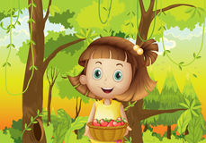 A young girl at the forest holding a basket of strawberries Stock Photo