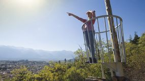 Young girl at forest navigation. Observation point above town pointing with hand Stock Photography