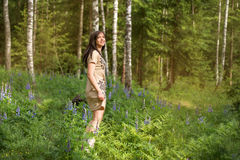 Young girl in a forest park whirl dances among flowers and birch trees Royalty Free Stock Photos