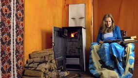 Young girl found interesting book and read near to the stove Stock Images