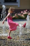 Young girl in fountain during - Fighting hot summer day`s temperature royalty free stock images