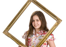Young girl in a frame. Young girl holding a picture frame around her face stock image