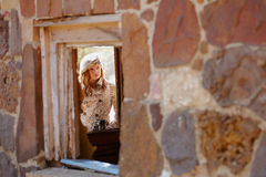 Young girl framed by window. Trendy young girl looking through windows of old stone house or home Royalty Free Stock Photos
