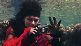 Young girl free diver in red dress photographs on camera underwater in Red Sea. Filming a movie. Actress smiling at camera. Extreme sport in marine landscape stock footage