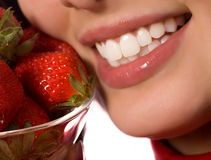 Young girl with a fresh strawberries. Womans smile with a fresh strawberries royalty free stock photo