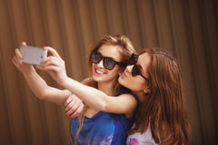 Young girl friends taking a self portrait using mobile phone Royalty Free Stock Images
