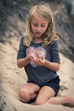 Young girl with frog on beach Royalty Free Stock Image