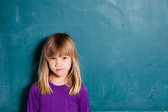 Young girl in front of chalkboard Stock Photo