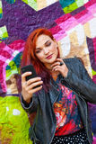 Young girl in front of graffiti making selfie royalty free stock images