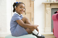 Young girl in front hallway fixing shoe and smilin