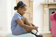 Young girl in front hallway fixing shoe and smilin royalty free stock images