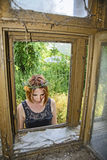 Young girl in front of an old window. Young woman in front of an old window in a house where she spent her childhood Stock Images