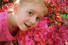 Young girl in front of pink flowers stock photos