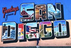 Young Girl in Front of San Diego Wall Mural. Young girl presenting herself in front of a life-sized San Diego postcard. Wall mural reads, `Greetings from San royalty free stock photos