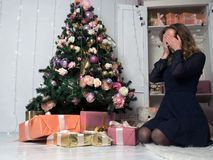 A young girl in front of a sitting in front of a Christmas tree, eyes closed with her hands in anticipation of choosing a gift. Stock Photo