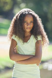 Young girl frowning with arms crossed in the park Royalty Free Stock Images
