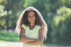 Young girl frowning at camera in the park Stock Photos