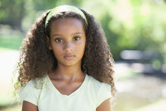 Young girl frowning at the camera in the park Stock Photo