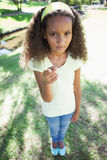 Young girl frowning and pointing at the camera in the park Stock Images
