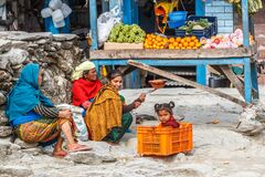 Young girl in a fruit box with family at their market stall