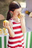 Young girl at fruit stand smelling a lemon Royalty Free Stock Images