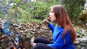 Young girl fry sausage on a fire outdoors and eat stock footage